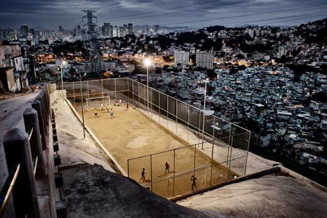 Eervolle vermelding Dagelijks leven, Series18 May 2012 © Frederik Buyckx, België voor De Standaard    Rio de Janeiro, Braziliaanse jeugd speelt op een voetbalveld, aangelegd onder een pacificatie programma in de La Mineira favela. De favela's (sloppenwijken) van Rio de Janeiro, Brazilië liggen vaak slechts één straat van de rijke buurten verwijderd. Ze waren jarenlang no-go-areas en werden overheerst door drugbazen en burgermilities. Wegens de kost van het WK Voetbal in 2014 en de Olympische Spelen in 2016 naar Rio, wilden de autoriteiten gezamelijk de favela's aanpakken.  Met dit doel voor ogen werd in 2009 de Unidade de Policia Pacificadora (UPP,'Vredestichtende Politie-Eenheid') opgericht. In de eerste fase, 'UPP Handhaving', werd een favela bestormd door elitetroepen, die een permanente politieaanwezigheid vestigden. Daarna volgde 'UPP Social', gericht op de verbetering van dienstverlening en infrastructuur, vijvoorbeeld in het onderwijs en de stroomvoorziening. Het initiatif kende wisselende successen. In sommige sloppenijken werden - vaak voor het eerst - politieposten gevestigd. Critici stellen echter dat de UPP zich op de favela's richtte die het dichtst bij de rijke buurten lagen en dat de sociale follow-up niet effectief was.